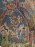The walls and ceiling of St.  George's Chapel on Lycabettos Hill are adorned with traditional colourful frescoes depicting Biblical scenes.